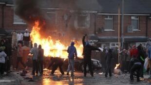 Foto de archivo: En el norte de Belfast, jóvenes nacionalistas lanzan coctelesjunto a un vehículo en llamas, del 12 de julio de 2011.