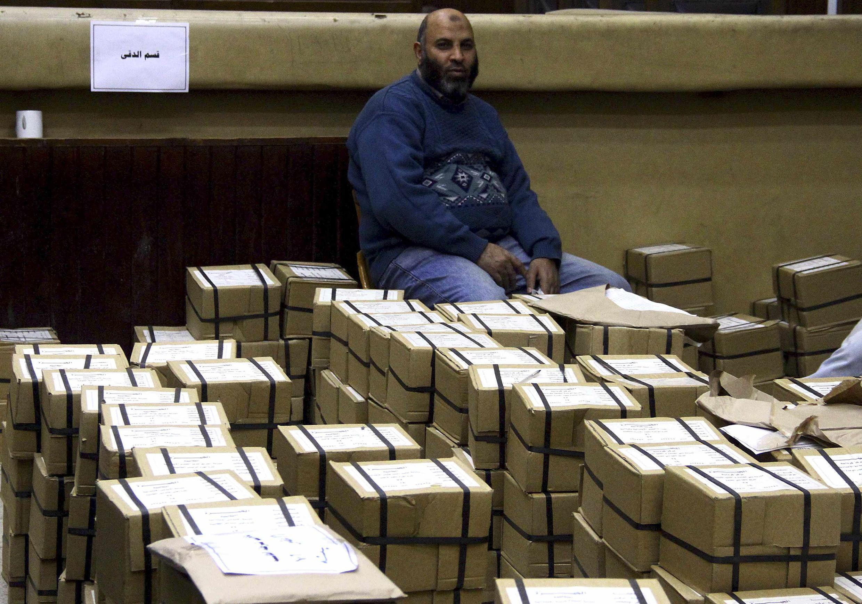 Un Egyptien assis devant des tas de bulletins pour le référendum sur la nouvelle Constitution le 14 janvier 2014.