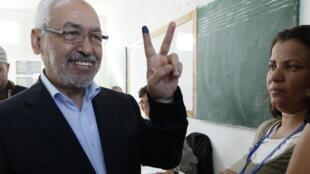 Rached Ghannouchi, líder do partido tunisiano Ennahda, faz o sinal da vitória após votar.