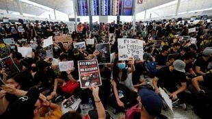 Anti-extradition bill demonstrators attend a protest at the departure hall of Hong Kong airport on 12 August, 2019.