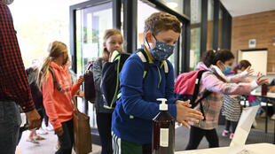 Estudantes usam álcool em gel na chegada à escola, em Estrasburgo, França.