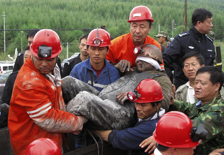 """黑龙江七台河""""8•23""""煤矿透水事故救援30日早晨取得重大进展,图为救援人员抬出在井下发现19名被困矿工之一。2011年8月30日。"""