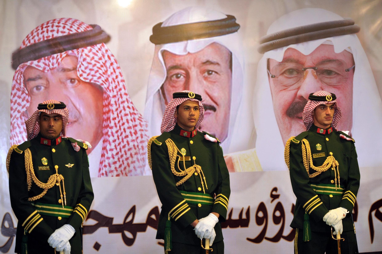 Des gardes royaux devant les portraits du roi défunt Abdallah ben Abdelaziz al-Saoud, Salman ben Abdelaziz al-Saoud et le prince héritier Moqren (photo datée de  février 2014).