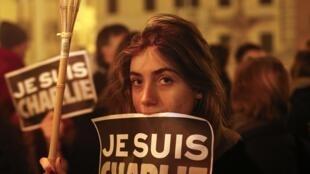 Face à l'ambassade de France à Rome, une jeune femme tient une pancarte «Je suis Charlie».