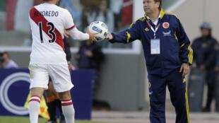 El ex DT de la selección colombiana, Hernán Darío Gómez 'El Bolillo', entrega la pelota al jugador peruano R.Revoredo, durante el partido de cuartos de final de la Copa de América, el 16 de julio de 2011.