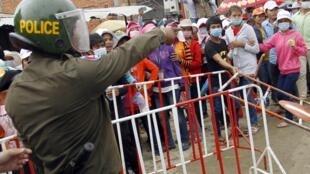 La police bloque les ouvriers du textile à Phnom Penh. Ils réclament des augmentations de salaires et de meilleures conditions de travail.