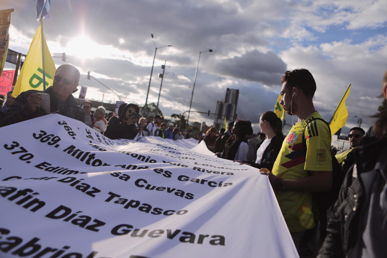Los manifestantes sostienen una larga lista de muertos durante la marcha en Bogotá el 26 de julio de 2019.
