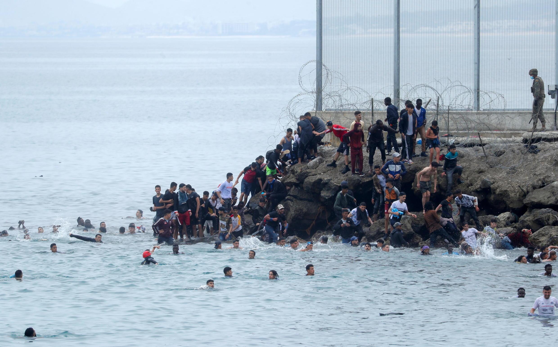 Des migrants, Marocains pour la plupart, tentent d'accoster sur les rives de Ceuta, enclave espagnole au Maroc, afin de passer la barrière de barbelés, le 18 mai 2021.