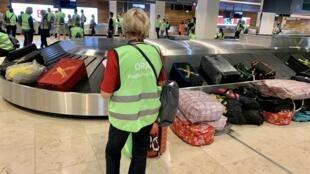 Une bénévole devant le tapis à bagages dans le nouvel aéroport de Berlin.
