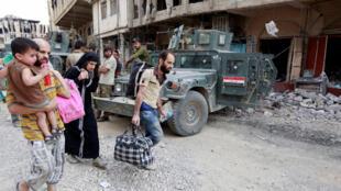Desplazados iraquíes que huyen de los enfrentamientos llevan sus pertenencias durante un enfrentamiento entre soldados iraquíes y yihadistas en la ciudad vieja de Mosul, el 7 de julio de 2017.