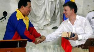 Venezuela's President Hugo Chavez shakes hands with his Colombian counterpart Juan Manuel Santos in Santa Marta
