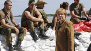 Angela Merkel visita a soldados alemanes, sentados sobre bolsas de arena para evitar el desborde del lago Goitzsche.