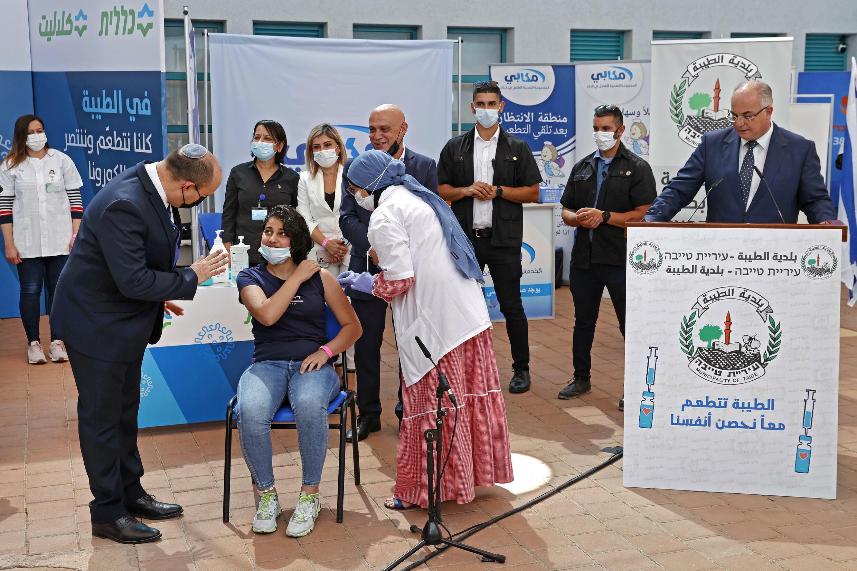 El primer ministro israelí, Naftali Bennett, habla con una joven mientras recibe una vacuna durante contra el covid-19 en una escuela secundaria de la ciudad de Taibeh, Israel, el 19 de agosto de 2021