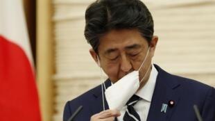 Le Premier ministre japonais Shinzo Abe enlève son masque avant une conférence de presse à Tokyo, le 25 mai 2020, au cours de laquelle il a annoncé la levée de l'état d'urgence dans l'ensemble du pays.
