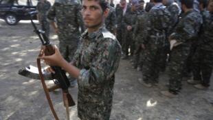 Voluntários da minoria yazid aprendem a manejar armas para combater extremistas.