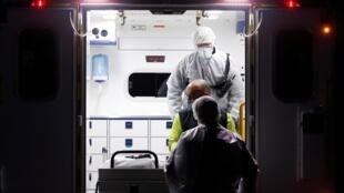 Un patient atteint du Covid-19 est secouru et transporté par du personnel de santé pendant une opération à Strasbourg, le 27 mars 2020.