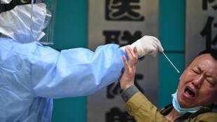 Un hombre que va a ser sometido a una prueba de coronavirus reacciona cuando un sanitario intenta tomarle una muestra el 16 de abril de 2020 en la ciudad china de Wuhan