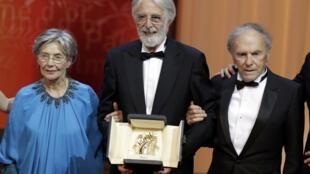 """Diretor Michael Haneke recebe a Palma de Ouro do Festival de Cannes 2012 ao lado dos atores Emanuelle Riva e Jean Louis Trintignant, protagonistas de """"Amor""""."""