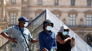 Des touristes près de la pyramide du Louvre à Paris, le 6 août 2020.