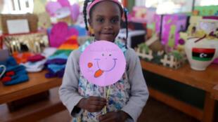 """""""Combato el cáncer con mi sonrisa"""", es el mensaje de esta niña. Libia, 11 de febrero de 2017."""