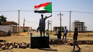 A Sudanese protester holds a national flag as he stands on a barricade along a street, demanding that the country's Transitional Military Council hand over power to civilians, in Khartoum, Sudan June 5, 2019