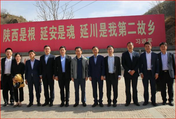 万达集团创始人、超级富豪王健林(中)等人在梁家河合影,背后横幅是习近平语录。