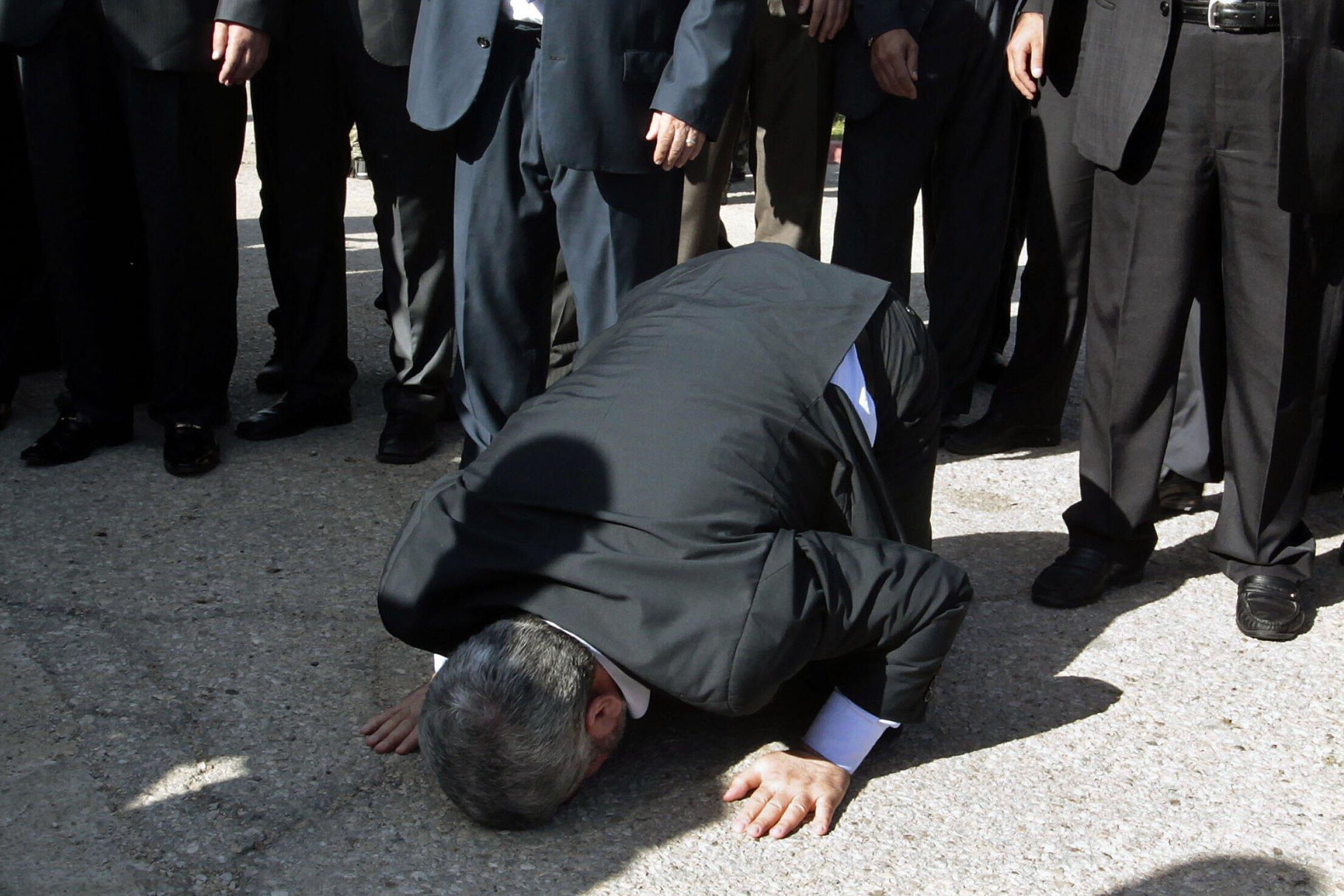 O líder do Hamas em exílio, Khaled Mechaal, reza ao pisar pela primeira vez 37 anos em solo palestino.