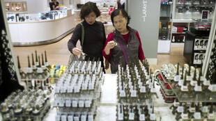 Chinese tourists look at Eiffel Tower souvenir at the Galeries Lafayette shopping center in Paris.