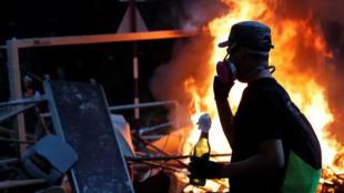2019年11月12日,在香港中文大学附近,抗议者手持燃烧瓶与防暴警察对峙。