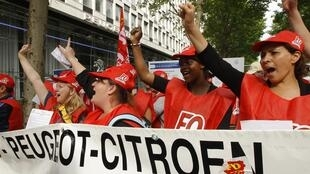 PSA Peugeot Citroën workers demonstrate outside the company's HQ
