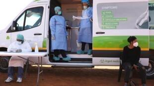 2020年4月21日,医护人员在一场筛查中等待患者到来,以抗击冠状病毒在南非扩散。Des membres du personnel médical attendent des patients lors d'une campagne de dépistage pour lutter contre la propagation du coronavirus à Lenasia, Afrique du Sud, le 21 avril 2020.