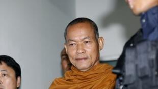 Le moine bouddhiste thaïlandais Phra Buddha Isara quitte les bureaux de la police escorté des forces de l'ordre après un interrogatoire à Bangkok, le 24 mai 2018.
