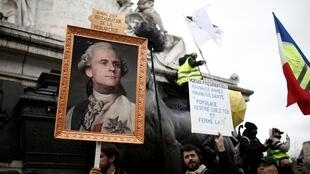 A striking French worker holds a portrait of French President Emmanuel Macron as King Louis XVI at a demonstration against pensions reform plans, Paris, 9 January 2020.