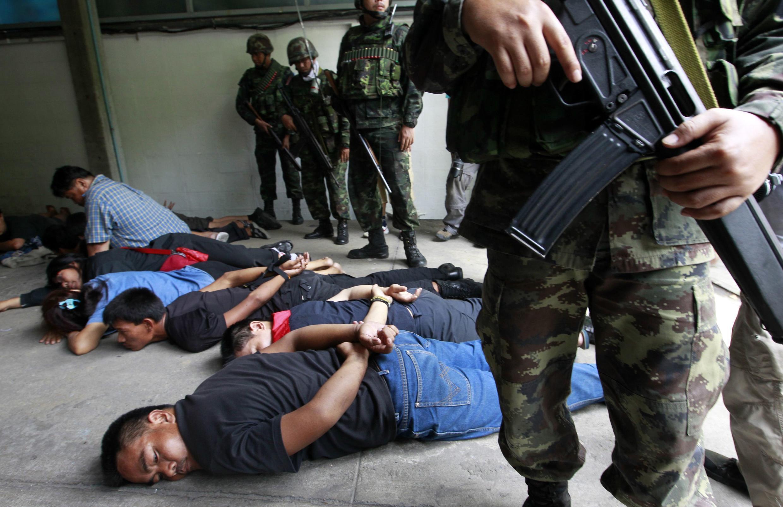 Soldados tailandeses detienen a varios manifestantes tras su rendición, Bangkok 19 de mayo de 2010.