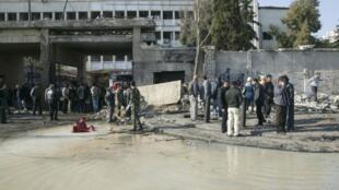 Passantes observam um prédio danificado após a explosão de um carro-bomba na manhã desta sexta-feira em Damasco.