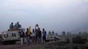 Des casques bleus de la brigade du Nord-Kivu de la MONUSCO en patrouille dans une rue de Goma croisent un groupe de jeunes en provenance d'un match de football, le 4 janvier 2013