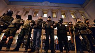 Des militants des groupes d'autodéfense de Maïdan montant la garde devant le Parlement ukrainien, à Kiev, le 24 février 2014.