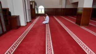 Un imam prie seul, à Tirana (Albanie), le 23 avril 2020, le premier soir du Ramadan. Les lieux de culte sont fermés au public suite aux mesures de prévention contre l'épidémie du coronavirus.