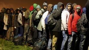 Des migrants attendent à l'entrée du centre de transfert, avant d'être évacués par autocar de la «jungle» de Calais, lundi 24 octobre 2016.