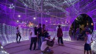 Personas posan para fotos en una plaza adornada de navidad en Caracas el 21 de diciembre
