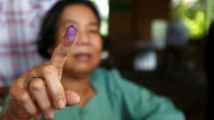 Eleitora cambojana mostra dedo colorido, após deixar impressão digital exigida aos eleitores neste domingo (29).