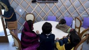 Des enfants  migrants regardent la télévision dans une salle commune du centre d'accueil pour réfugiés d'Ivry-sur-Seine, en banlieue parisienne, le 8 février  2017.