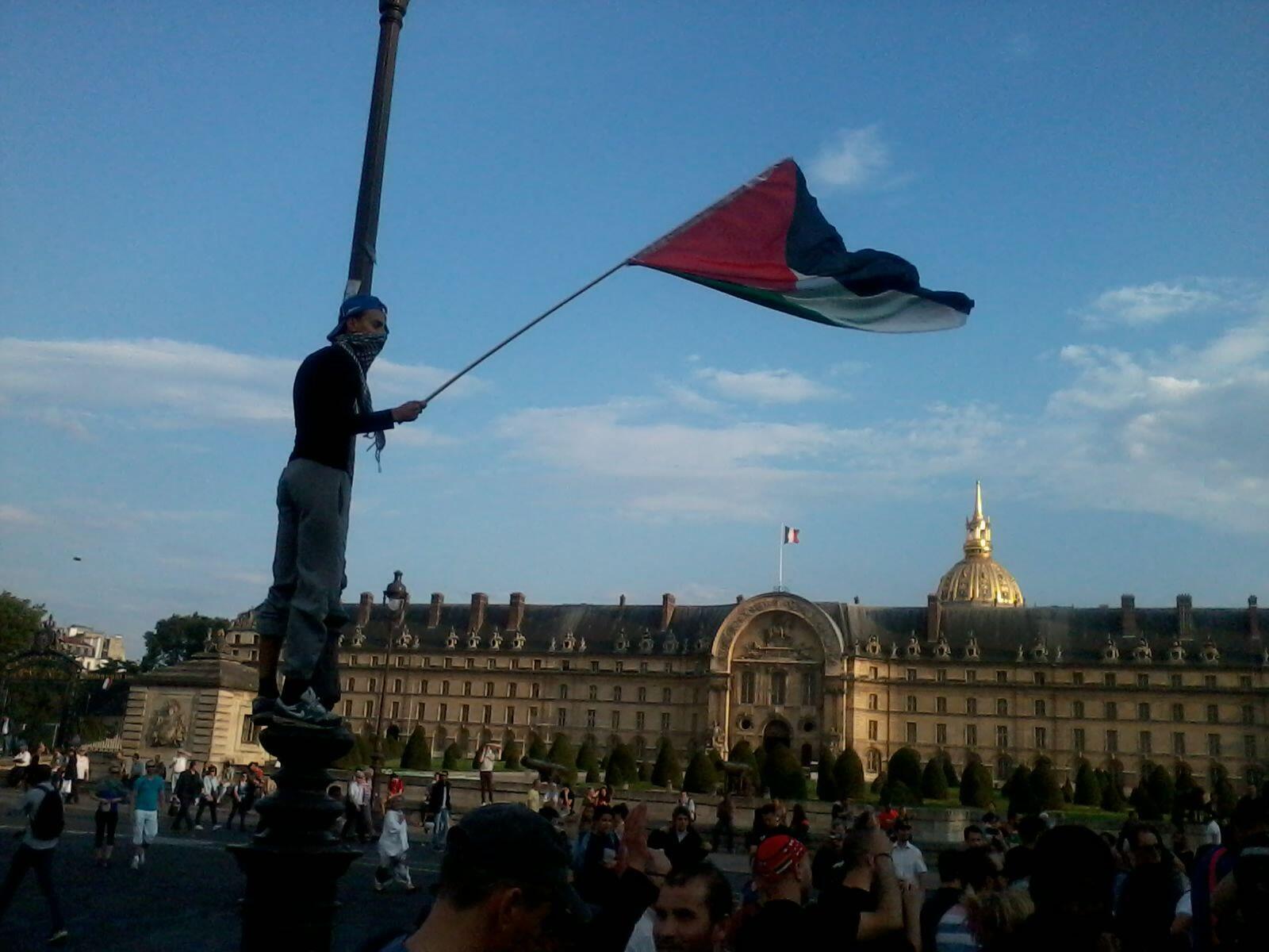 Manifestante com bandeira palestina em frente ao Hôtel des Invalides