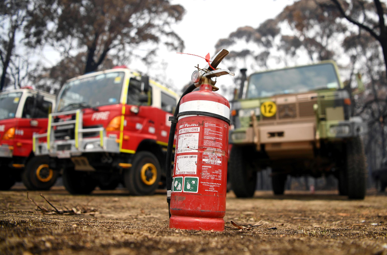 Một xe quân sự đậu kế một xe chửa cháy tại Mallacoota ngày 10/01/2020.