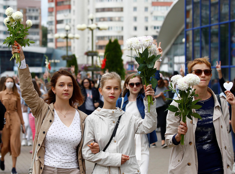В центре Минска утром 12 августа около 200 женщин в белой одежде с цветами выстроились в живую цепь в знак солидарности с протестующими.