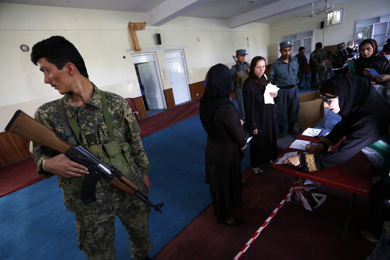 Décompte des voix après la clôture du scrutin, sous la surveillance d'un soldat de l'armée afghane, le 14 juin 2014, dans un bureau de police à Kaboul.