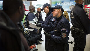 Police conduct identity checks on a group of men in the Gare du Nord in Paris on November 30, 2012.