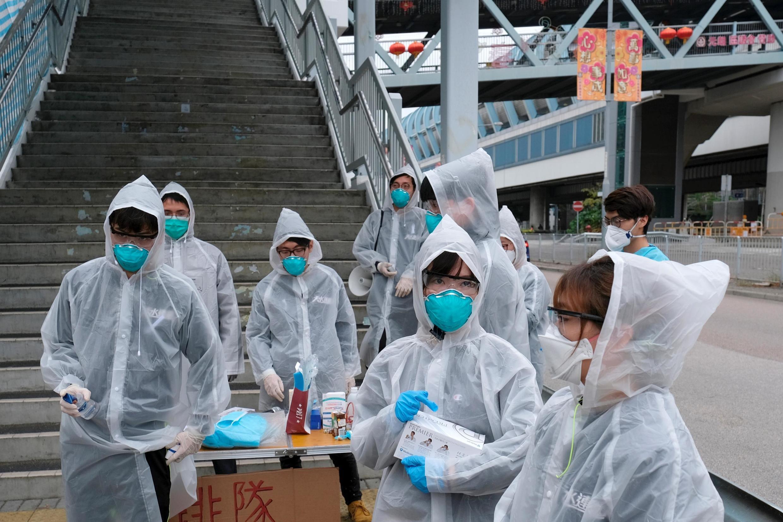香港發現新的冠狀病毒之後,戴着口罩和雨衣的居民自願對行人進行體溫監測 2020年2月4日