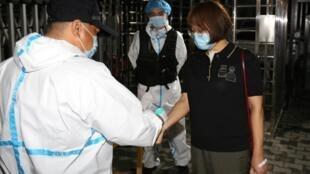 Travailleur mesurant la température corporelle d'une femme à l'entrée d'un complexe résidentiel, à Urumqi, dans le Xinjiang.