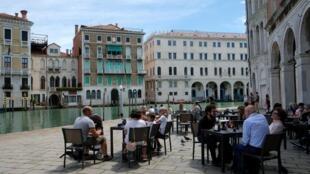 Des touristes prennent leur déjeûner sur la terrasse d'un restaurant de Venise, le 24 mail 2020.